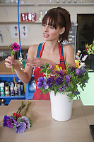 Florist arranges flowers in a vase