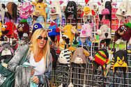 OCTOBER 22, 2011 - MERRICK, NY: Young woman looking at colorful animal knit hats on display at booth at Merrick Street Fair, New York, USA.
