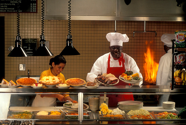 Stock photo of a restaurant chef holding plates of prepared food at the counter
