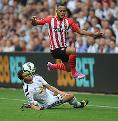 Swansea City's Angel Rangel Sliding tackles Southampton's Ryan Bertrand - Photo mandatory by-line: Alex James/JMP - Mobile: 07966 386802 20/09/2014 - SPORT - FOOTBALL - Swansea - Liberty Stadium - Swansea City v Southampton  - Barclays Premier League