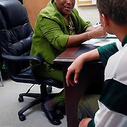 African American Female Dean of Students for Disciple Action Counseling, Court Probation officer and Athletic Director talking with student in her office for disciple action counseling