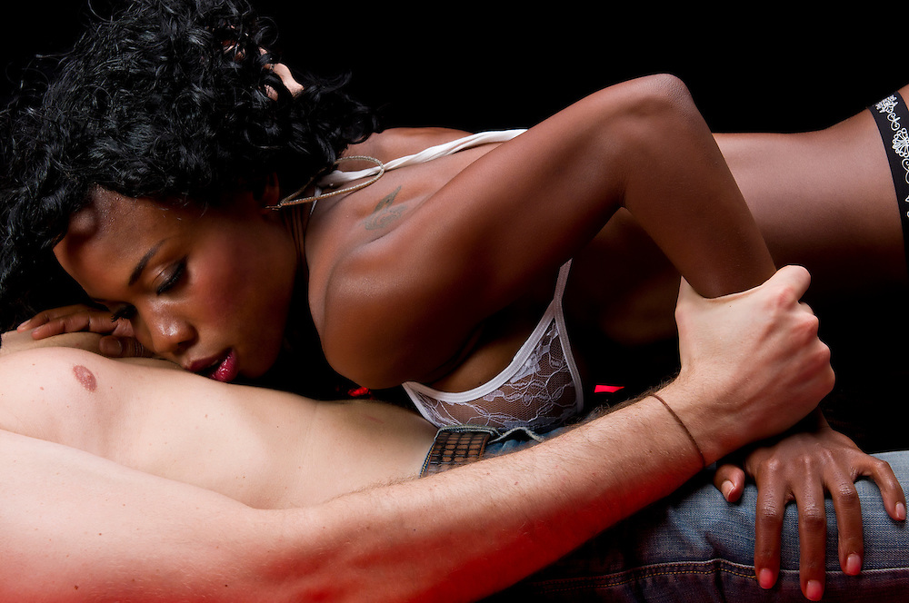 Multiracial couple in sensual erotic foreplay.
