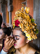22 JULY 2016 - TENGANAN DUAH TUKAD, BALI, INDONESIA: A girl gets into her traditional costume and makeup in the Tenganan Duah Tukad village on Bali before the Pandanus fights. The ritual Pandanus fights are dedicated to Hindu Lord Indra. Men engage in ritual combat with spiky pandanus leaves and rattan shields. They usually end up leaving bloody scratches on the combatants' backs. The young girls from the community wear their best outfits to watch the fights. The fights have been traced to traditional Balinese beliefs from the 14th century CE. The fights are annual events in the Balinese year, which is 210 days long, or about every seven months in the Gregorian calendar.    PHOTO BY JACK KURTZ