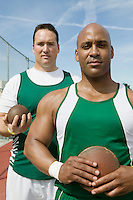 Two male athletes holding shot and discus, portrait