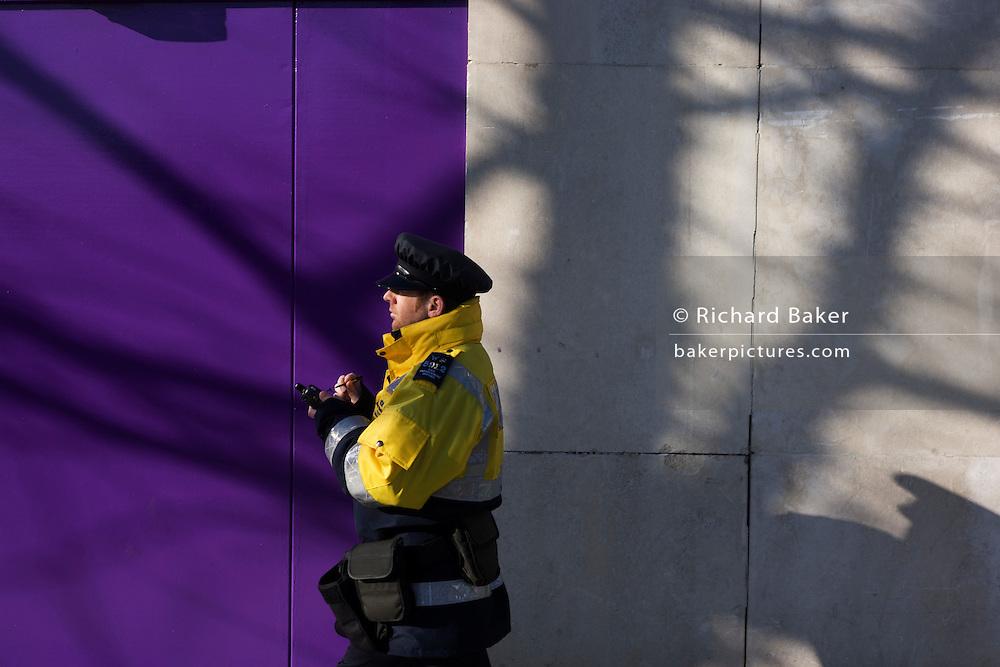 A Civil Parking Enforcement Officer walks past a purple construction hoarding screen on a London street.