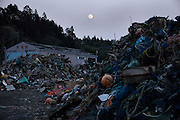 Full moon and debris of fishing equipments at a fishing port in Minamisanriku town.