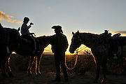 Riders and their horses take in the sunset in the Sonoran Desert, Tucson, Arizona, USA.