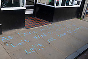 As the Coronavirus pandemic lockdown eases and small shops and businesses re-open, a quote from 1980s British band, The Police's song 'Don't Stand So Close To Me' has been chalked on to the pavement outside a bar, asking customers to keep their social distance, on 19th July 2020, in Whitstable, Kent, England.