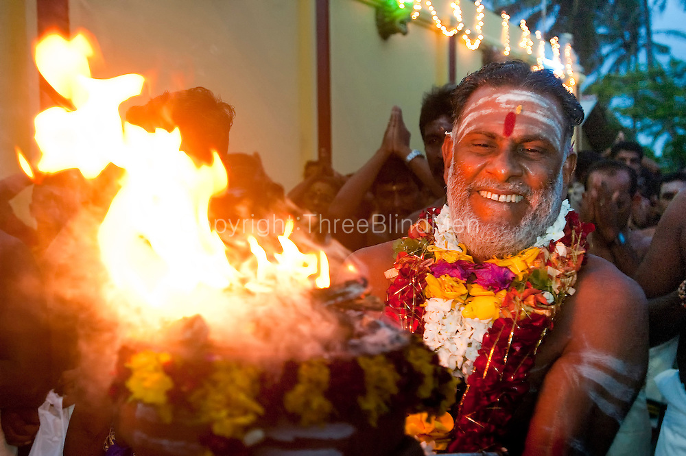Sri Lanka. On the dawn of the last day of the festival, the Head Priest carries out the flame to light the wood for the fire walking. Festival at Udappu village.