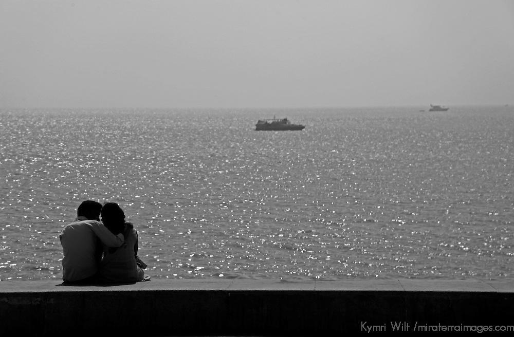 Asia, India, Mumbai. Romantic couple watches sunset at Chowpatty Beach.