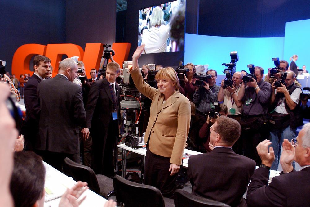 11 NOV 2002, HANNOVER/GERMANY:<br /> Angela Merkel, CDU Bundesvorsitzende, nimmt nach ihrer Wiederwahl den Applaus der Delegierten entgegen, CDU Bundesparteitag, Hannover Messe<br /> IMAGE: 20021111-01-115<br /> KEYWORDS: Parteitag, party congress, Jubel, Fotografen, Fotojournalisten, photographer, Kamera, Camera