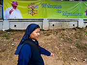 17 NOVEMBER 2017 - YANGON, MYANMAR: A Catholic nun walks past a poster welcoming Pope Francis to Myanmar. Pope Francis is visiting Myanmar for three days in late November, 2017. He is participating in two Catholic masses and expected to address the Rohingya issue.      PHOTO BY JACK KURTZ
