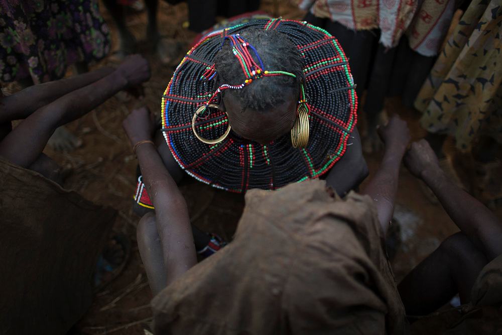 A Pokot woman performs a circumcision on a girl.