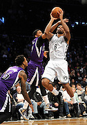 Brooklyn Nets' Alan Anderson (6) shoots past Sacramento Kings' Rudy Gay (8) and Ben McLemore (16) during an NBA basketball game on Sunday, March 9, 2014 at Barclays Center in New York. (AP Photo/Kathy Kmonicek)