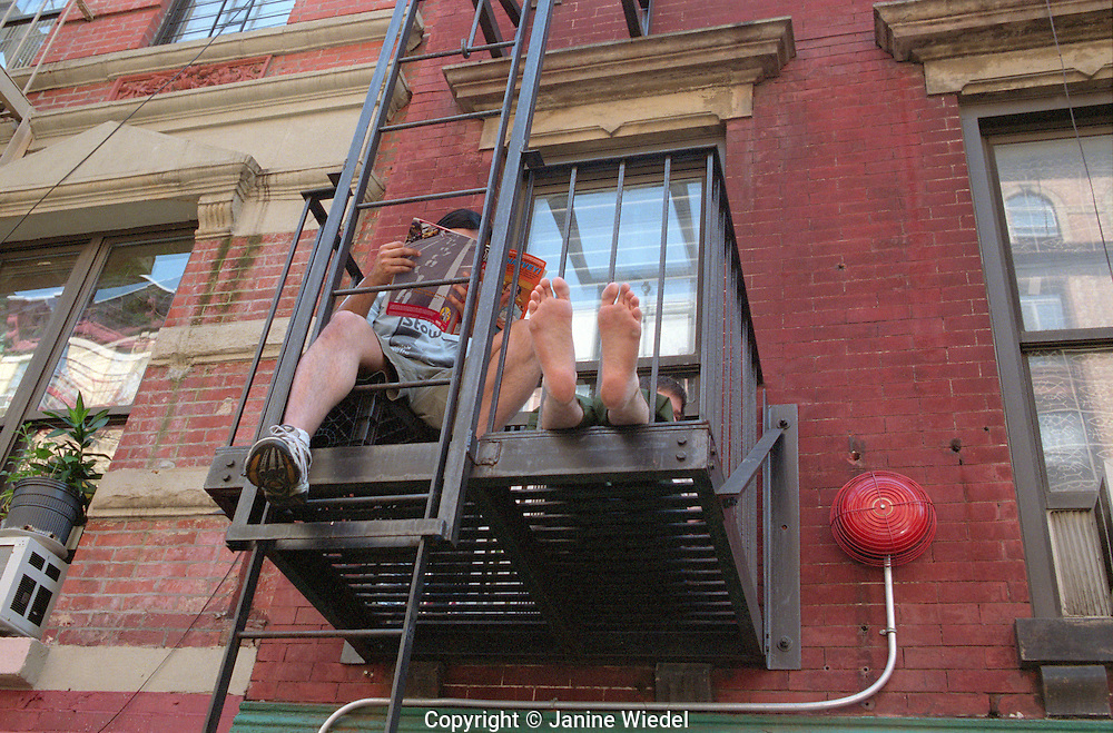 Two men resting from the midday heat on New York fire escape.