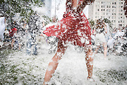 A women wearing a red dress participates in International Pillow Fight at Pershing Square on Saturday, April 2, 2011in downtown Los Angeles. (Photo by Michael Yanow)