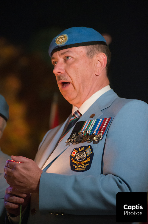 A veteran speaks while holding a candle during the vigil. October 25, 2014.