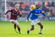 Glen Kamara (#18) of Rangers FC shields the ball from Ryotaro Meshino (#77) of Heart of Midlothian FC during the Ladbrokes Scottish Premiership match between Heart of Midlothian and Rangers FC at Tynecastle Park, Edinburgh, Scotland on 20 October 2019.