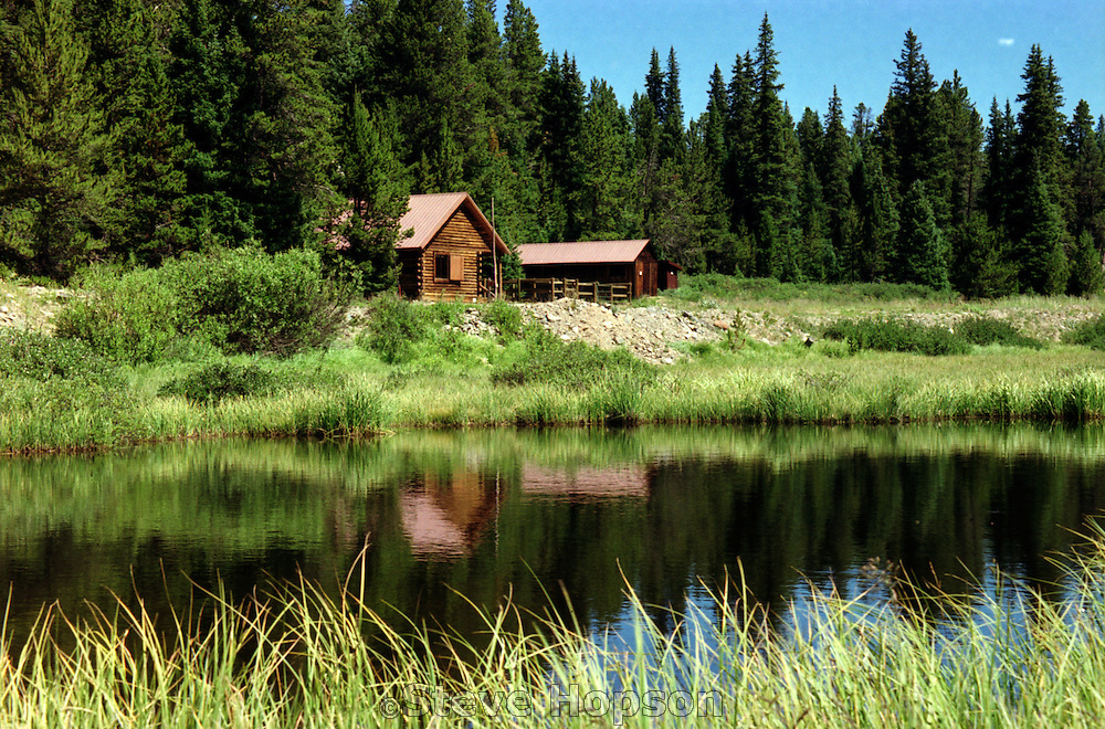 A Ranger cabin in the Rocky Mountains National Park in Colorado is reflected in an alpine lake, July 27, 2002.