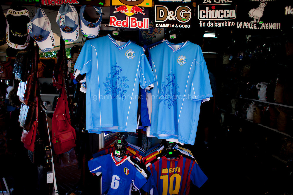 NOTE: EXPLICIT ITALIAN T-SHIRTS on top of the frame. SAN MARINO, SAN MARNO - 3 OCTOBER 2011: Two jerseys of the San Marino national team are on sale in tourist shop in San Marino, San Marino on October 3, 2011. The San Marino national football team is the last team in the FIFA  World Ranking (position 203). San Marino, whose population reaches 30,000 people, has never won a game since the team was founded in 1988. They have only ever won one game, beating Liechtenstein 1&ndash;0 in a friendly match on 28 April 2004. The Republic of San Marino, an enclave surronded by Italy situated on the eastern side of the Apennine Moutanins, is the oldest consitutional republic of the world<br /> <br /> <br /> ph. Gianni Cipriano