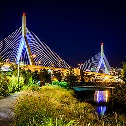 Boston Zakim Bunker Hill Bridge at night photo with a park walkway. The Leonard P. Zakim Bunker Hill Memorial Bridge is a cable bridge that spans the Charles River in Boston, Massachusetts in the Eastern United States or America. Copyright ⓒ Paul Velgos with All Rights Reserved.