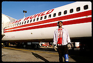 Ramp service worker poses beside TWA jet parked at concourse of Lambert Intl Airport; St. Louis. Missouri