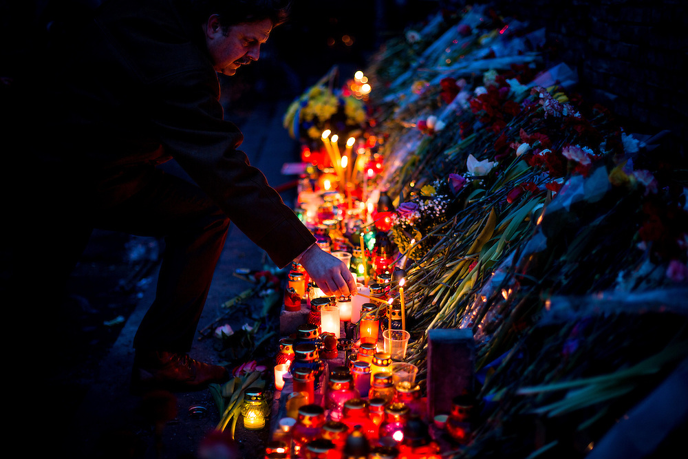 "A man lights up a candle on an improvised memorial to the ""heroes of Maïdan"", on the Independance Square, in Kiev."