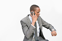 African American businessman checking time while on a call