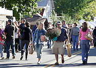 Sugar Loaf, New York - A couple carries items they purchased as they walk down a closed street during the Sugar Loaf Fall Festival on Oct. 10, 2010. ©Tom Bushey / The Image Works