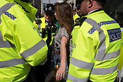 A protester is arrested and searched by Met police officers at Oxford Circus on day 4 of protests by climate change environmental activists with pressure group Extinction Rebellion, on18th April 2019, in London, England.