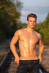 hot lean man without a shirt on railroad tracks at sunset