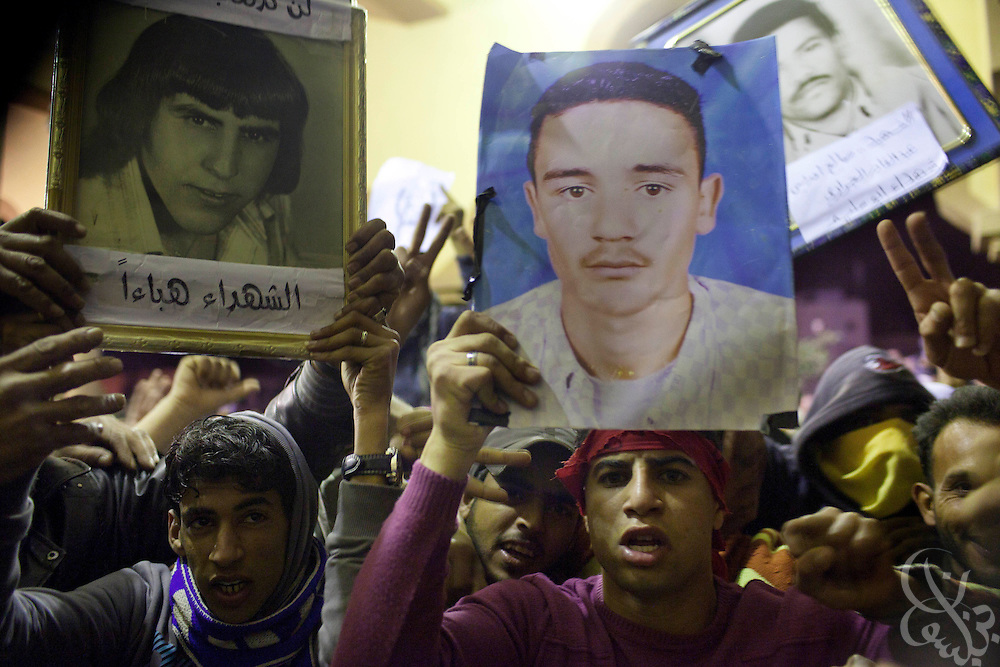 Libyan youths hold pictures of martyrs during nighttime protests in Tobrouk, Libya February 22, 2011. Protests that began in Libya February 17 have spread across the country and threaten to bring down the 42 year regime of Libyan leader Col. Qaddafi. .Slug: Libya.Credit: Scott Nelson for the New York Times