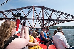 Tourists photograph the Forth Bridge from Maid of the Forth ship  at South Queensferry in Scotland, UK