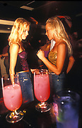 Two Glamourous and pretty looking women dancing together in a cocktail bar, UK 2000's