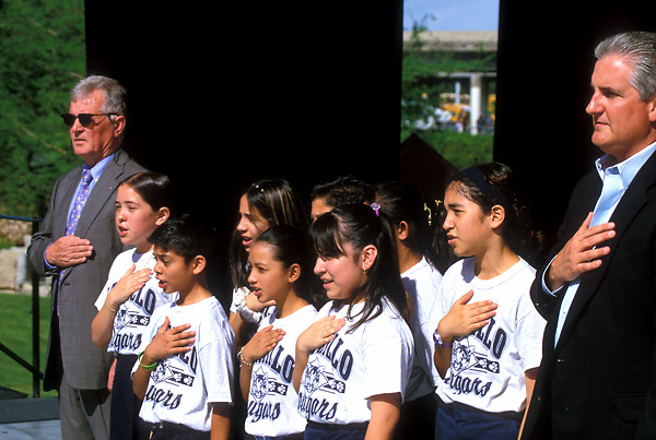 Stock photo of school children saying the pledge of allegiance outside