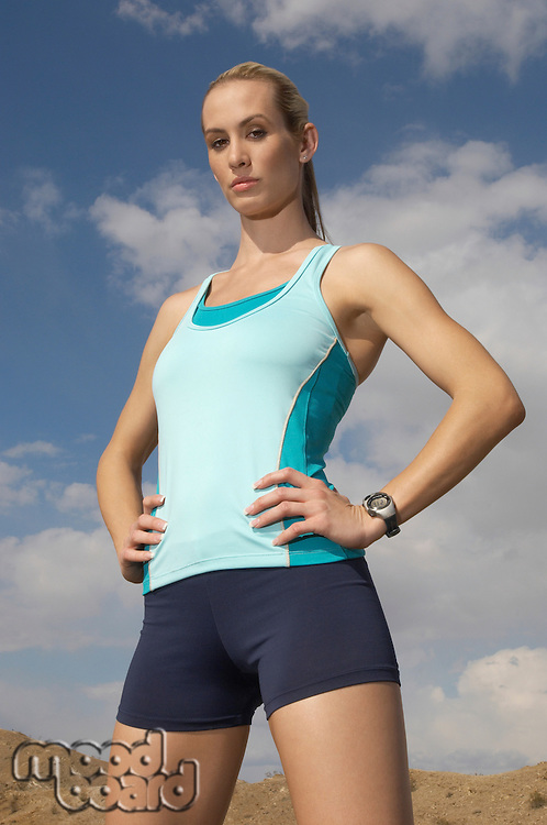 Female jogger with hands on hips, outdoors, portrait