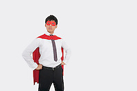Confident Asian businessman in superhero costume