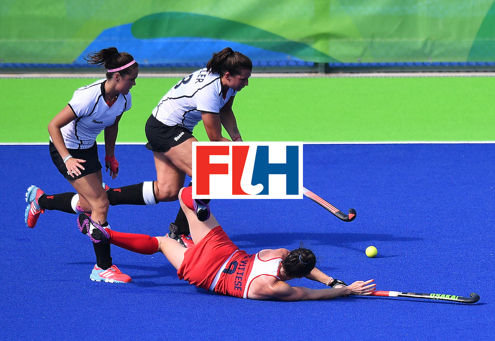 Germany's Julia Muller (C) vies with The USA's Michelle Vittese (bottom) during the women's quarterfinal field hockey USA vs Germany match of the Rio 2016 Olympics Games at the Olympic Hockey Centre in Rio de Janeiro on August 15, 2016. / AFP / Carl DE SOUZA        (Photo credit should read CARL DE SOUZA/AFP/Getty Images)