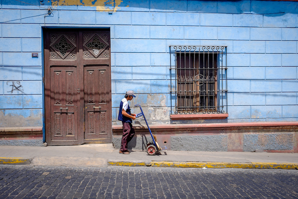 AREQUIPA, PERU - CIRCA APRIL 2014: Man walking with hand cart on typical street of Arequipa. Arequipa is the Second city of Perú by population with 861,145 inhabitants and is the second most industrialized and commercial city of Peru.