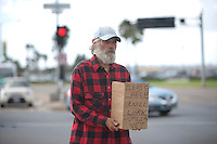 Homeless person with sign on street