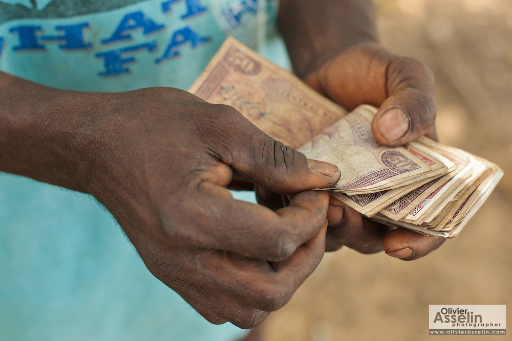 A man counts money he's just received from a UNICEF-sponsored social cash transfer programme in the village of Julijuah, Bomi county, Liberia on Tuesday April 3, 2012. Beneficiary households receive monthly transfers that vary according to the size of the household, with additional sums provided for each child enrolled in school. Families are selected for participation in the programme based on two key criteria: they must be both extremely poor and labour-constrained.