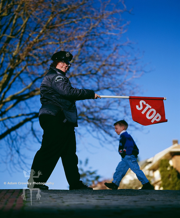Female Crossing Guard holding up stop sign, portrait