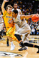 November 13th, 2013:  Colorado Buffaloes junior guard Spencer Dinwiddie (25) drives against University of Wyoming Cowboys junior guard Riley Grabau (2) in the second half of action in the NCAA Basketball game between the University of Wyoming Cowboys and the University of Colorado Buffaloes at the Coors Events Center in Boulder, Colorado