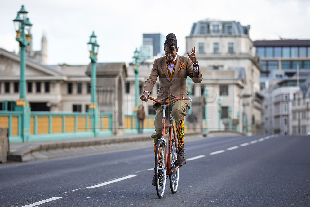 © Licensed to London News Pictures. 04/05/2019. London, UK. A man raises his hand as he cycles across Southwark Bridge on the Tweed Run bike ride in Central London. The annual event sees hundreds of people cycle around the capital past various landmarks wearing vintage tweed outfits. Photo credit: Rob Pinney/LNP