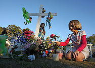 BRENDAN FITTERER  |  Times.PT_330383_FITT_triplet_3 (11/08/2010 HUDSON) (IMAGING NOTE: PLEASE PRESERVE WARM TONES/SHADOWS FROM EVENING LIGHT).Marissa Manuli, 9, right, tends to a memorial in her front yard for Delaney Rossman, a 5-year-old triplet killed in a Friday night accident on Kings Manor Avenue in Hudson when she and other children were struck by a Jeep. Delaney's sister, Gabrielle, was critically injured. Manuli, escaped with minor injuries. Isabella Rossman, a third triplet, was shoved out of the way by her older sister, Victoria Morgan, and was scraped and bruised. (In the background is Manuli's sister, Sabrina Manuli, 10)