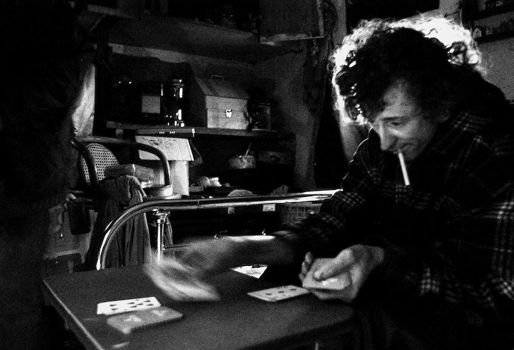Thomas Holtman, 22, plays solitaire in the dilapidated trailer he shares with his mother. Jobless, Holtman spends his time at the park playing with children.