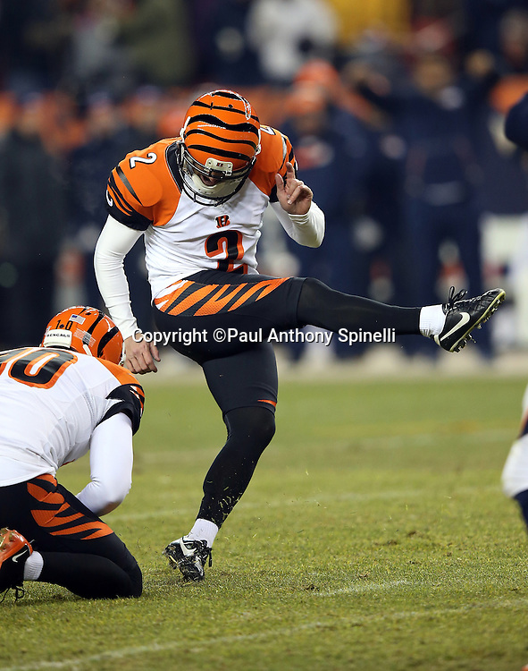 Cincinnati Bengals punter Kevin Huber (10) holds while Cincinnati Bengals kicker Mike Nugent (2) kicks a late fourth quarter field goal that ties the score at 17-17 during the 2015 NFL week 16 regular season football game against the Denver Broncos on Monday, Dec. 28, 2015 in Denver. The Broncos won the game in overtime 20-17. (©Paul Anthony Spinelli)