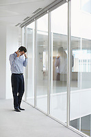 Office worker talking on mobile phone head down at window of empty office space