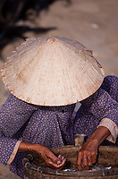 Woman with a coracle hat soring fish on China Beach.