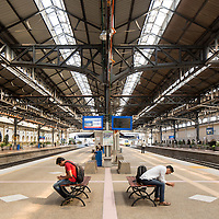 Asia, Malaysia, Kuala Lumpur, Two men sit checking mobile telephones inside cavernous train station